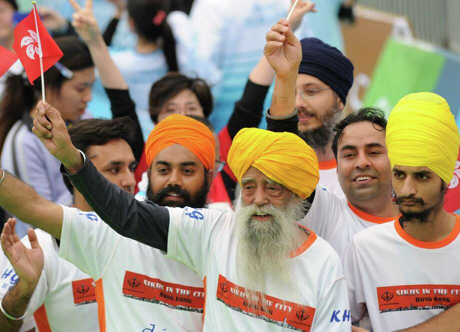 TOPSHOTS Indian-born British national Fauja Singh (C) waves a Hong Kong flag after crossing the finish line in the 10-km event as part of the Hong Kong Marathon on February 24, 2013. The 101-year-old Sikh believed to be the world's oldest marathon runner said on February 21 after arriving in the southern Chinese territory that he felt sad to be retiring from competitive events, as he prepared for his last race in Hong Kong.     AFP PHOTO / Dale de la ReyDALE de la REY/AFP/Getty Images Photo: DALE DE LA REY, AFP/Getty Images / AFP