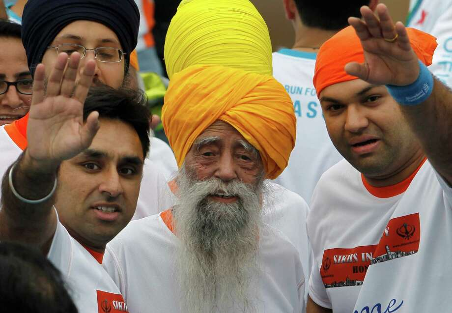 Centenarian marathon runner Fauja Singh, 101, center, originally from Beas Pind, in Jalandhar, India but who now lives in London, smiles after finishing a 10-kilometer race, held as part of the annual Hong Kong Marathon, in Hong Kong Sunday, Feb. 24, 2013. Singh will retire from public racing after competing in the marathon. Photo: Vincent Yu, AP / AP