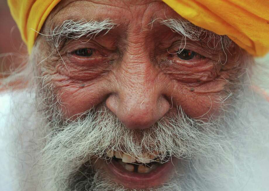 Indian-born British national Fauja Singh speaks to the media after crossing the finish line in the 10-km event as part of the Hong Kong Marathon on February 24, 2013. The 101-year-old Sikh believed to be the world's oldest marathon runner said on February 21 after arriving in the southern Chinese territory that he felt sad to be retiring from competitive events, as he prepared for his last race in Hong Kong.     AFP PHOTO / Dale de la ReyDALE de la REY/AFP/Getty Images Photo: DALE DE LA REY, AFP/Getty Images / AFP