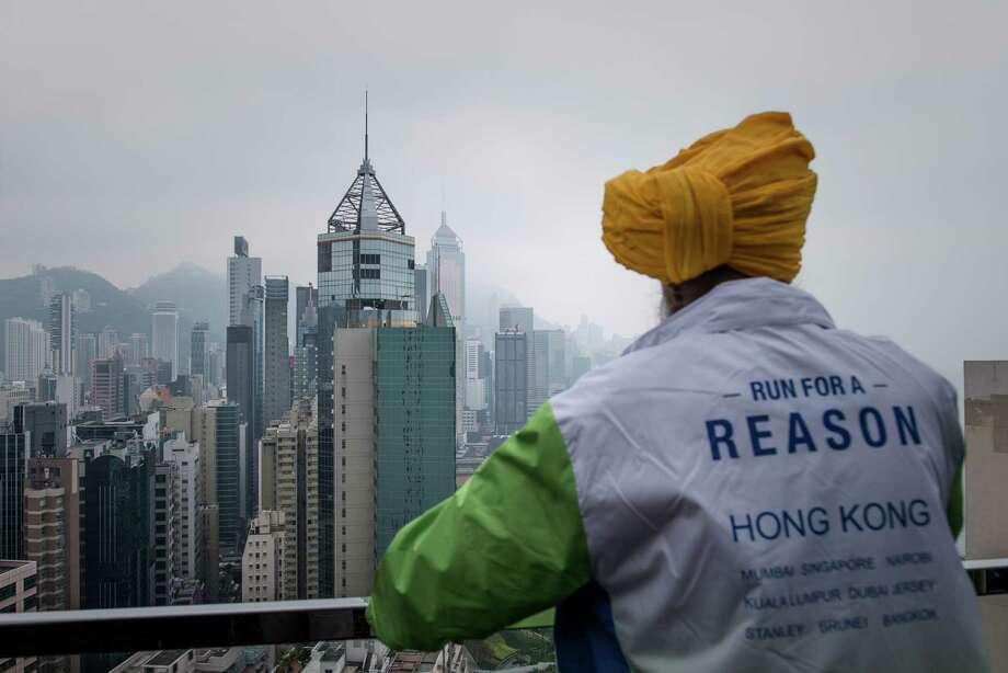 "Indian-born British national Fauja Singh looks at the city's skyline in Hong Kong on February 21, 2013.  The 101-year-old Sikh regarded as the world's oldest marathon runner said he was ""hurt"" over his retirement plan as he feared people will forget him, ahead of his last race to take place in Hong Kong on February 24.  AFP PHOTO / Philippe LopezPHILIPPE LOPEZ/AFP/Getty Images Photo: PHILIPPE LOPEZ, AFP/Getty Images / F AFP"