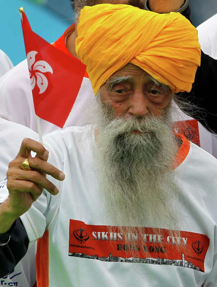 Centenarian marathon runner Fauja Singh, 101, center, originally from Beas Pind, in Jalandhar, India but who now lives in London, raises a Hong Kong flag after finishing a 10-kilometer race, which was part of the annual Hong Kong Marathon, in Hong Kong Sunday, Feb. 24, 2013. Singh will retire from public racing after competing in the marathon. Photo: Vincent Yu, AP / AP
