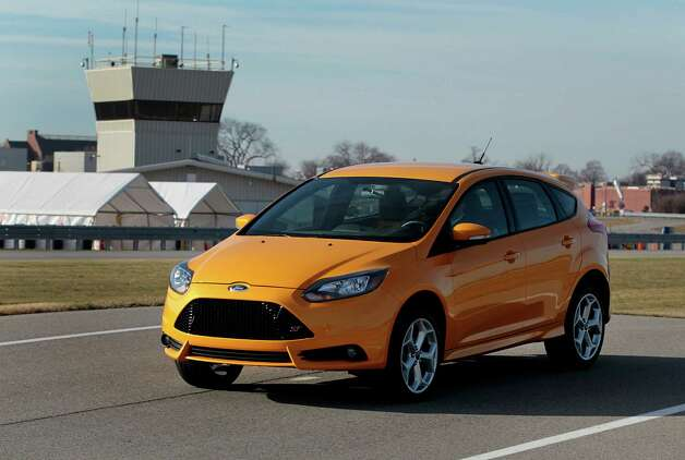 "The 2013 Ford Motor Co. Focus ST vehicle in a color called ""tangerine scream"" sits parked on the test track at the company's Dearborn Development Center in Dearborn, Michigan, U.S., on Thursday, Dec. 13, 2012. Ford's Dearborn Development Center opened in 2006 after a $43 million transformation of the company's historic Dearborn Proving Grounds facility. Photographer: Jeff Kowalsky/Bloomberg Photo: Jeff Kowalsky, Bloomberg / © 2012 Bloomberg Finance LP"