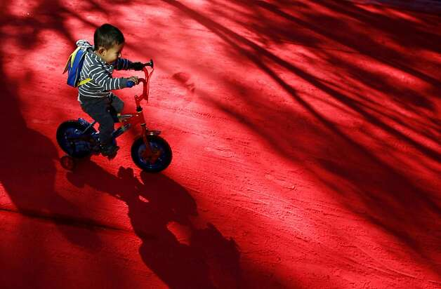 "A boy rides his bicycle along Reforma Avenue which is covered by red dust spread by a detergent company in Mexico City, Sunday, Feb. 24, 2013. Thousands of cyclists, skaters, pedestrians and pets take over Mexico City's Reforma Avenue during ""bicycle Sundays.""  Photo: Marco Ugarte, Associated Press"