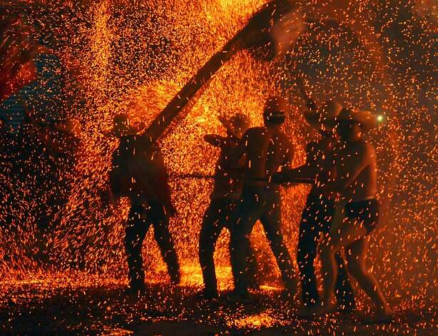 "People take part in the traditional dragon dance in the molten iron on February 24, 2013 in Dazhou, Sichuan Province of China. The dragon dance in the molten iron, ""Wu Huo Long"" in Chinese, is a traditional custom to celebrate the Lantern Festival. The Chinese Lunar New Year also known as the Spring Festival, which is based on the Lunisolar Chinese calendar, is celebrated from the first day of the first month of the lunar year and ends with Lantern Festival on the Fifteenth day. 2013 is the Year of the Snake according the 12-year cycle of animals which appear in the Chinese Zodiac. Photo: ChinaFotoPress, Getty Images"