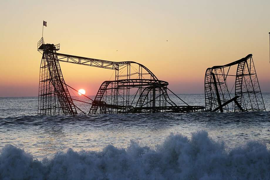 The sun rises in Seaside Heights, N.J., Monday, Feb. 25, 2013, behind the Jet Star Roller Coaster which has been sitting in the ocean after part of the Funtown Pier was destroyed during Superstorm Sandy. The private owners of the amusement pier that collapsed in Seaside Heightsare working with insurers to devise a plan to dismantle the ride and get it out of the ocean.  Photo: Mel Evans, Associated Press
