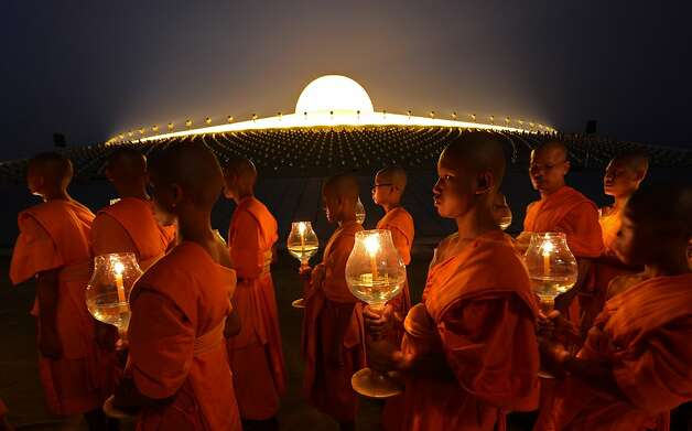 Buddhist monks hold candles as they walk around a Pagoda on Makha Bhucha Day at the Dhammakaya Temple in Pathumthani province on February 25, 2013. Makha Bhucha day is observed in Thailand on the full moon of the third lunar month and commemorates the day when 1,250 monks gathered to be ordained by the Buddha.  Photo: Pornchai Kittiwongsakul, AFP/Getty Images