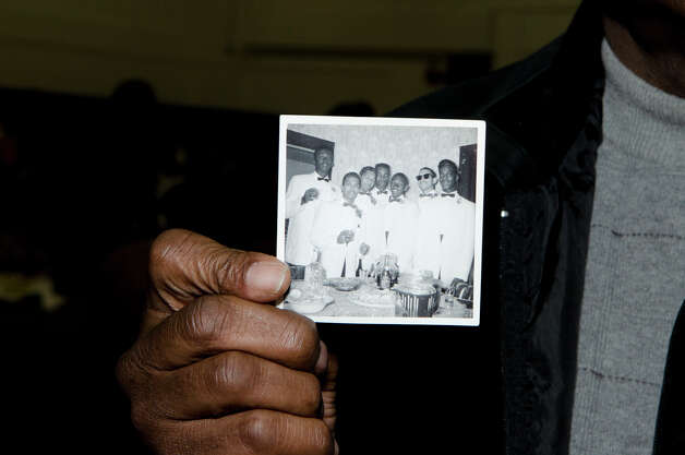 Fletcher Summers, of Norwalk, holds up a photograph of him and his friends from their youth during the Carver Center's 75th anniversary alumni reunion at the center in Norwalk on Friday, Feb. 22, 2013. Summers, third from right, attended the center in the 1950s. Photo: Amy Mortensen / Connecticut Post Freelance