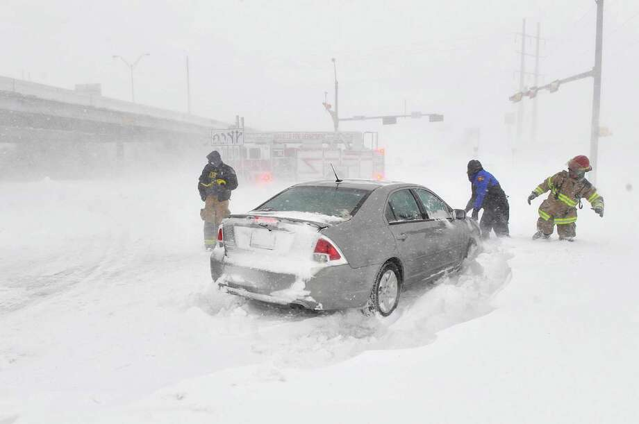 Amarillo emergency personnel assist a stranded motorist on the I-40 service road Monday, Feb. 25, 2013. A blizzard packing 50 mph wind gusts and more than 11 inches of snow blasted Amarillo and Texas Panhandle Monday, Feb. 25, 2013, making travel nearly impossible. Interstate 40 and many major highways in the Panhandle have been closed. (AP Photo/The Amarillo Globe News,Michael Schumacher) Photo: Michael Schumacher, Associated Press / Amarillo Globe-News