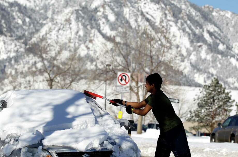 Adnan Reza, a senior engineering student at the University of Colorado, from Dhaka, Bangladesh, removes the snow from his car on a sunny morning following a winter storm, in Boulder, Colo., Monday Feb. 25, 2013. Coloradoans are digging out from a major snowstorm that canceled flights, delayed opening of Denver city offices and piled up snow as much as two-feet deep.(AP Photo/Brennan Linsley) Photo: Brennan Linsley, Associated Press / AP
