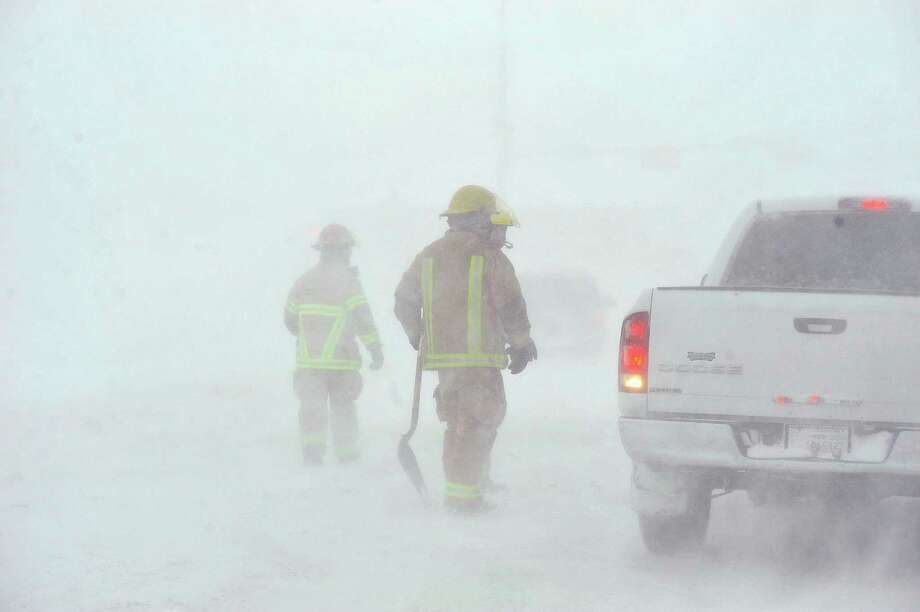 Amarillo emergency personnel assisted a stranded motorist on the I-40 service road Monday, Feb. 25, 2013 in Amarillo, Texas. A blizzard packing 50 mph wind gusts and more than 11 inches of snow blasted Amarillo and Texas Panhandle Monday, making travel nearly impossible. Interstate 40 and many major highways in the Panhandle have been closed. (AP Photo/The Amarillo Globe News,Michael Schumacher) Photo: Michael Schumacher, Associated Press / Amarillo Globe-News