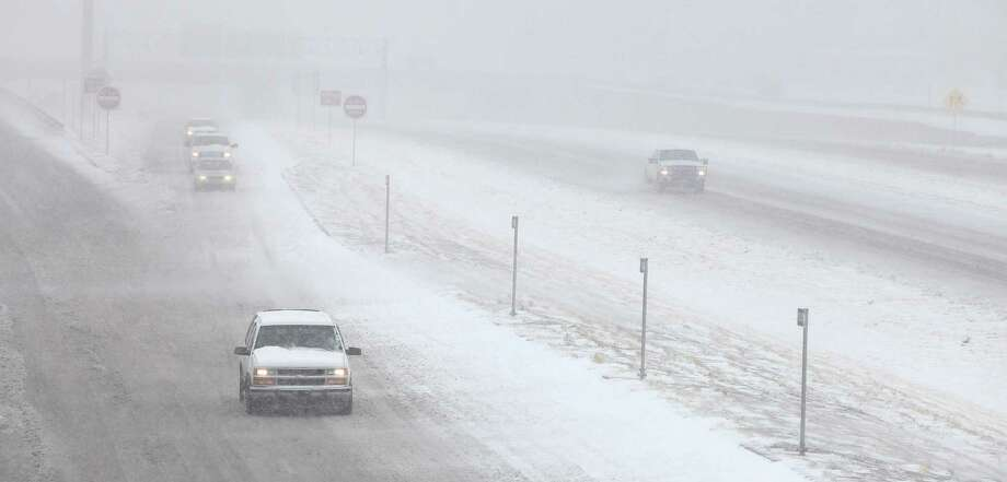 Vehicles move along in blizzard conditions in Lubbock, Texas, Monday, Feb. 25, 2013.  State troopers are unable to respond to calls for assistance and National Guard units are mobilizing as a winter storm blankets the central Plains with a foot of snow in some places. Roads are closed Monday throughout West Texas and the Panhandle. (AP Photo/Lubbock Avalanche-Journal, Zach Long) Photo: Zach Long, Associated Press / Lubbock Avalanche-Journal