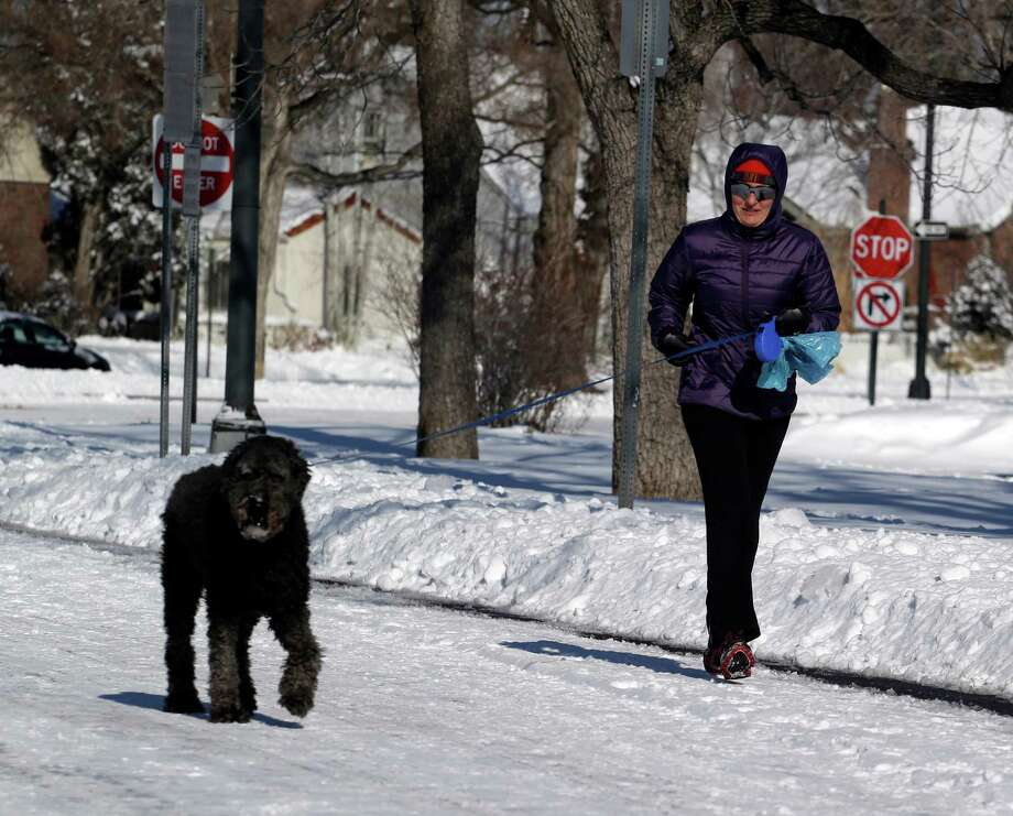 Jennifer Korman jogs with her dog in Denver on Monday, Feb. 25, 2013. A winter storm passed through Colorado on Sunday dumping over a foot of snow in the Denver area.  (AP Photo/Ed Andrieski) Photo: Ed Andrieski, Associated Press / AP