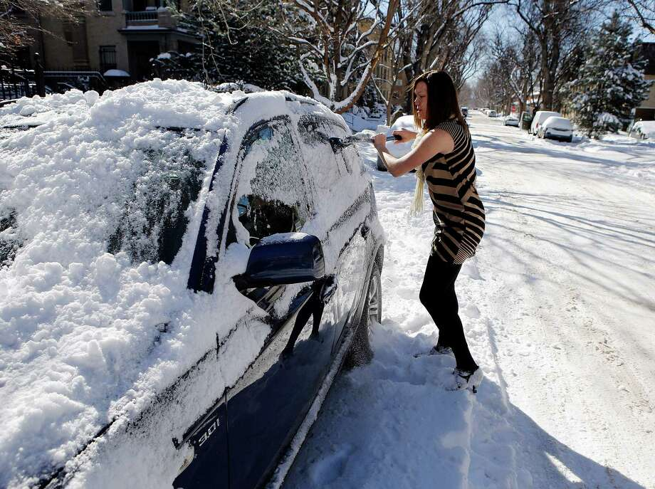 Ayla Anderson, clears snow from her vehicle in Denver on Monday, Feb. 25, 2013. Anderson just moved to Denver from Florida. A winter storm passed through Colorado on Sunday dumping over a foot of snow in the Denver area.  (AP Photo/Ed Andrieski) Photo: Ed Andrieski, Associated Press / AP