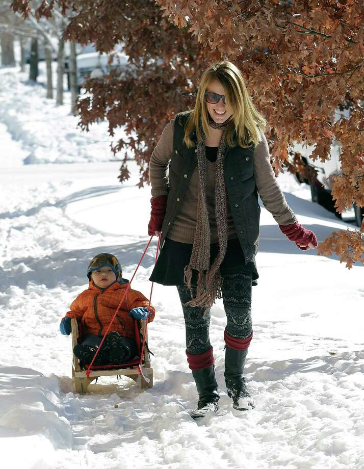Babysitter Faith Whitney pulls two-year-old Teddy through the snow on a sled in Denver on Monday, Feb. 25, 2013. A winter storm passed through Colorado on Sunday dumping over a foot of snow in the Denver area. (AP Photo/Ed Andrieski) Photo: Ed Andrieski, Associated Press / AP