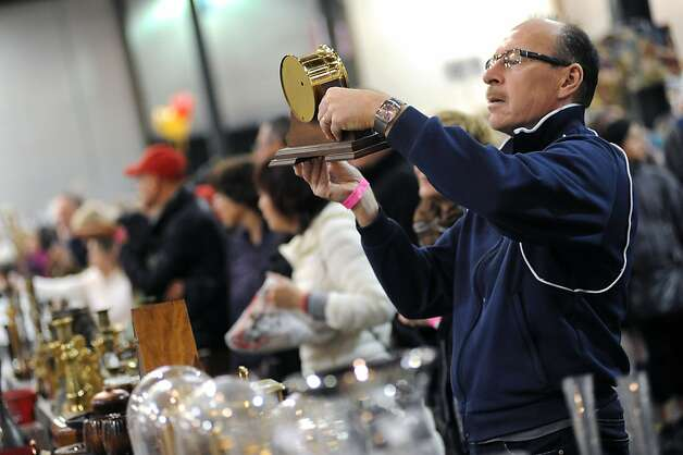 Howard Czapla of San Ramon, CA inspects a clock as he shops during the benifit sale.  The annual White Elephant Sale preview benefiting the Oakland Museum opened today to large crowds in Oakland, CA Sunday January 27th, 2013. Photo: Michael Short, Special To The Chronicle