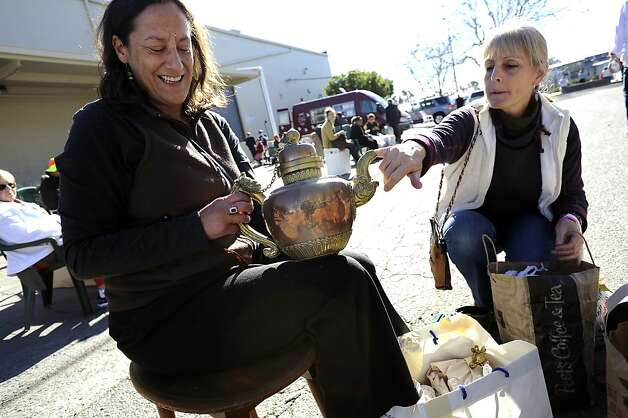 Anne Lewis(R) pokes at the copper tea pot her friend Elsie Levi is holding as they sift through their purchases while sitting outside the sale.  The annual White Elephant Sale preview benefiting the Oakland Museum opened today to large crowds in Oakland, CA Sunday January 27th, 2013. Photo: Michael Short, Special To The Chronicle