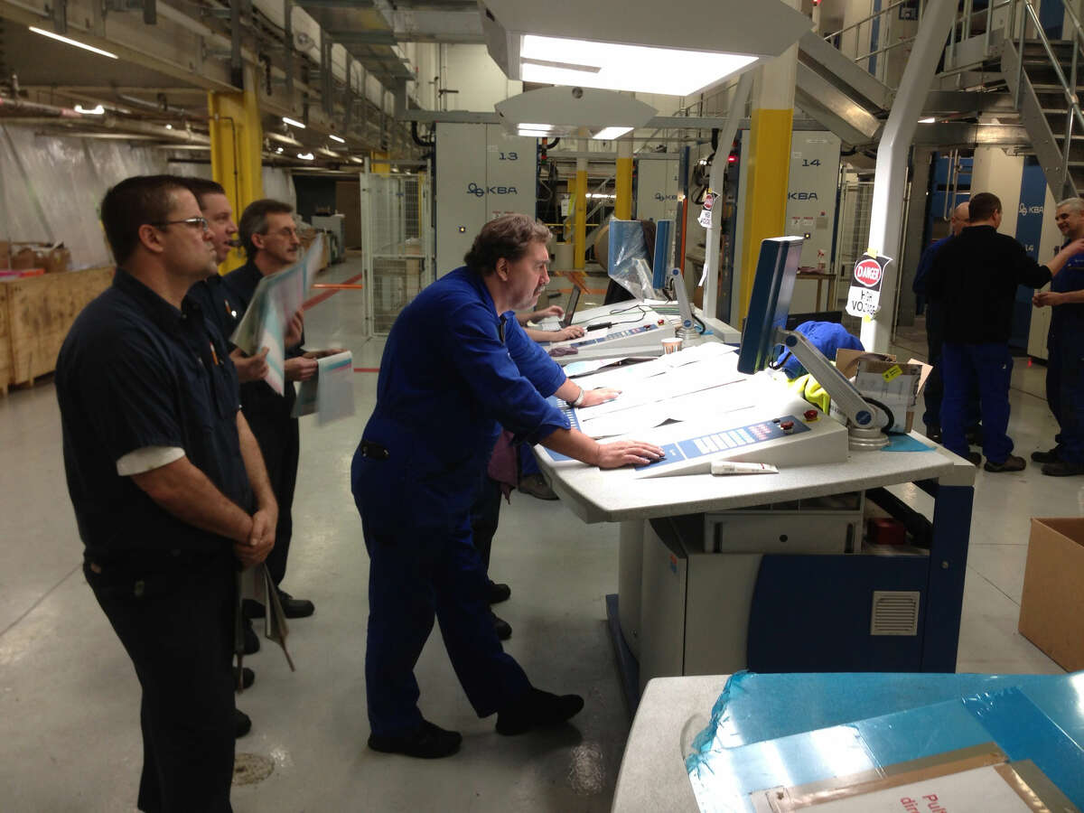 First Ink: A milestone was reached on Saturday, Feb. 23, when ink was first run on the new press at the Times Union. A worker looks over some of the sample pages at one of the control stations. The new press is scheduled to begin operation during the second half of March.
