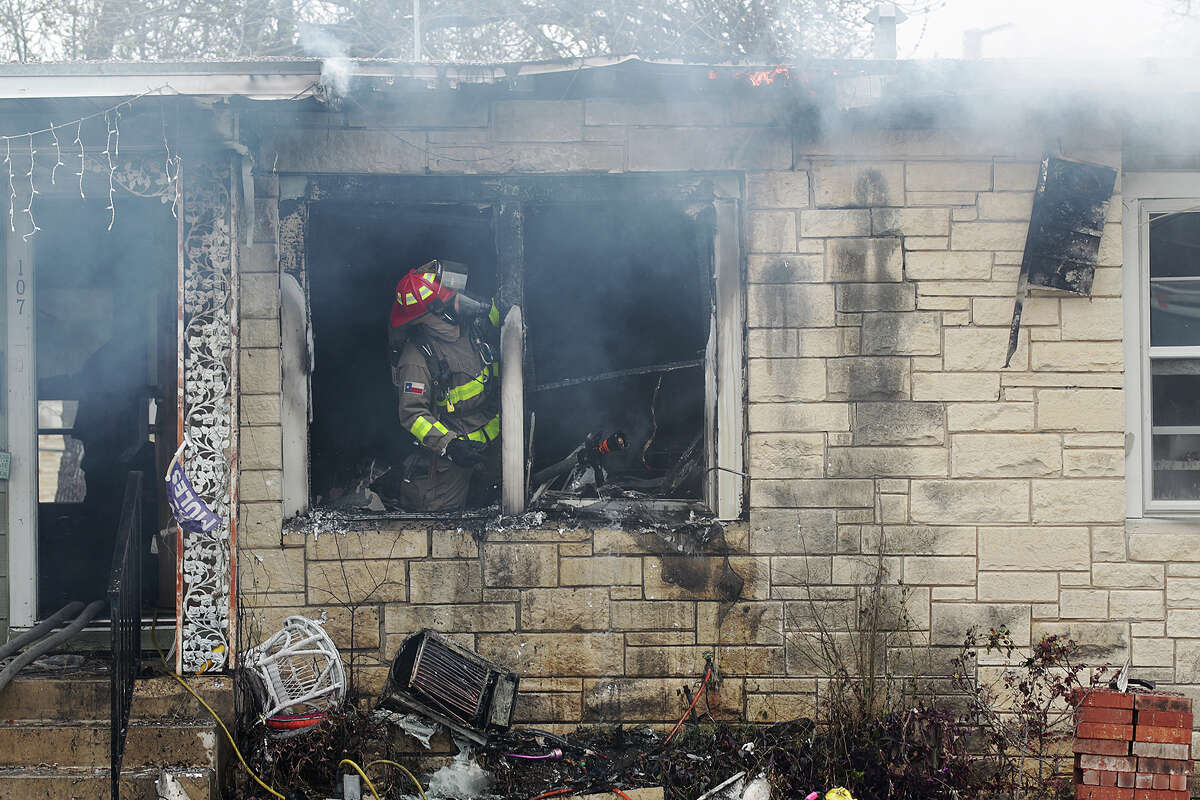 Emergency personnel put out hot spots during a multi-structure fire at the 8100 block of Old Pearsall Road, Monday, Feb. 25, 2013. The fire was fueled by high winds.