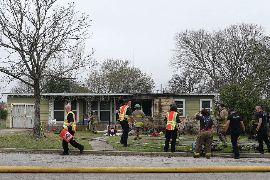 A man tries to catch the attention of emergency personnel as he runs to put out a hot spot during a multi-structure fire at the 8100 block of Old Pearsall Road, Monday, Feb. 25, 2013. The fire was fueled by high winds. Photo: JERRY LARA, San Antonio Express-News / © 2015 San Antonio Express-News