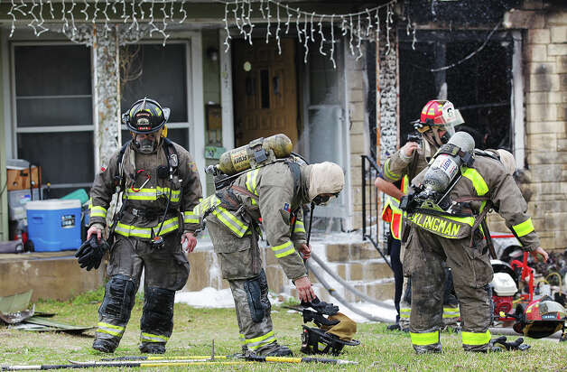 A woman carries a dog as emergency personnel battle a multi-structure fire at the 8100 block of Old Pearsall Road, Monday, Feb. 25, 2013. The fire was fueled by high winds. Photo: Jerry Lara, San Antonio Express-News / ©2013 San Antonio Express-News