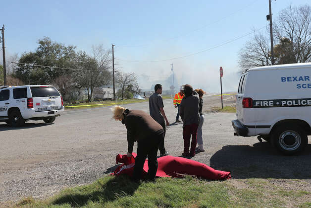 A elderly woman is comforted as emergency personnel battle a multi-structure fire at the 8100 block of Old Pearsall Road, Monday, Feb. 25, 2013. The fire was fueled by high winds. The woman was pulled out of a house next to the burning structures. Photo: Jerry Lara, San Antonio Express-News / ©2013 San Antonio Express-News