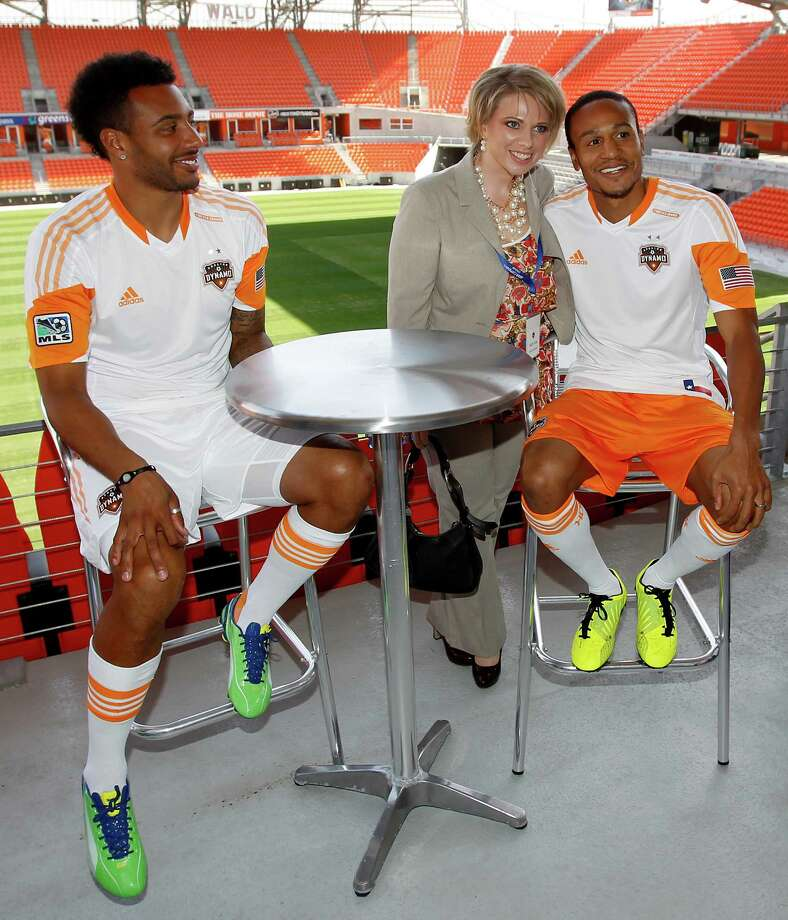 2/25/13: Houston Dynamo Giles Barnes watches as Heather Fricke has her photo taken with Ricardo Clark at the new Houston Dynamo uniform unveiling at BBVA Stadium in Houston Texas. The new uniforms are a lighter material and have two stars above the Dynamo logo representing the two MLS Cup Championships and a Texas Flag on the bottom of the shirt. Photo: Thomas B. Shea, For The Chronicle / © 2012 Thomas B. Shea