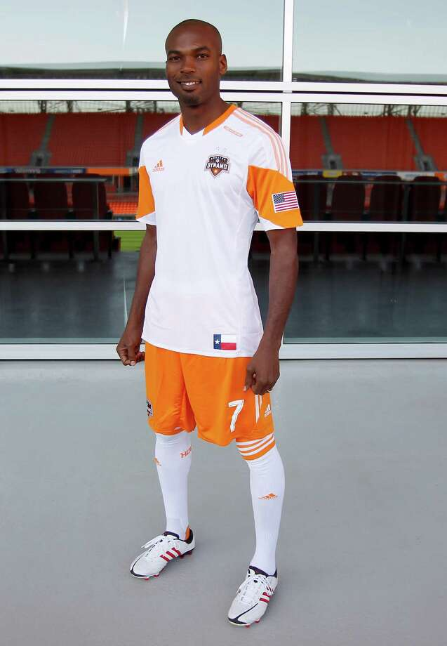 2/25/13: Houston Dynamo and newly acquired player Omar Cummings (7) poses with one of the new uniforms at the  Houston Dynamo uniform unveiling at BBVA Stadium in Houston Texas. The new uniforms are a lighter material and have two stars above the Dynamo logo representing the two MLS Cup Championships and a Texas Flag on the bottom of the shirt. Photo: Thomas B. Shea, For The Chronicle / © 2012 Thomas B. Shea
