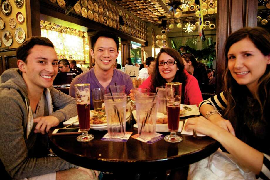 Charie Ramirez, Julius L., Rosana Oliveira, and Hannah Sulik are eating a late night snack and having a few beers at the Flying Saucer Draught Emporium.