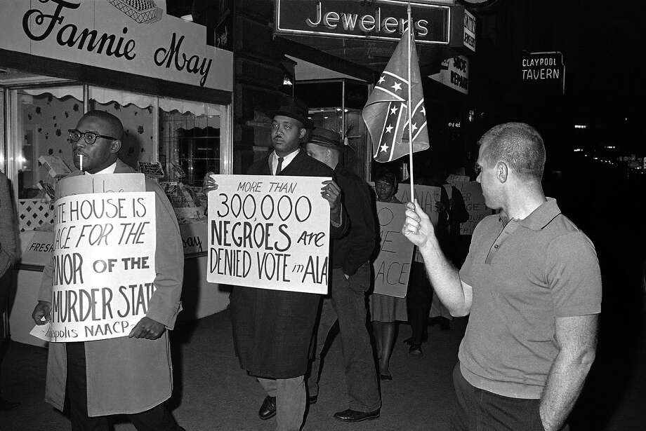"FILE - In this April 14, 1964 black-and-white file photo, a man holds a Confederate flag at right, as demonstrators, including one carrying a sign saying: ""More than 300,000 Negroes are Denied Vote in Ala"", demonstrate in front of an Indianapolis hotel where then-Alabama Governor George Wallace was staying. After more than a century, the Census Bureau is dropping use of the word ""Negro"" to describe black Americans in its surveys. Instead of the term popularized during the Jim Crow era of racial segregation, census forms will use the more modern-day labels, ""black"" or ""African-American"".  (AP Photo/Bob Daugherty, File) Photo: Bob Daugherty, Associated Press"