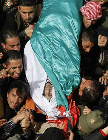 Palestinians carry the body of Arafat Jaradat during his funeral in the West Bank town of Saeer, near Hebron, Monday, Feb. 25, 2013. Thousands have attended the funeral procession of a 30-year-old Palestinian man who died under disputed circumstances in Israeli custody. Palestinian officials say autopsy results show Jaradat was tortured by Israeli interrogators, while Israeli officials say there's no conclusive cause of death yet and that more tests are needed. (AP Photo/Nasser Shiyoukhi) Photo: Nasser Shiyoukhi, Associated Press