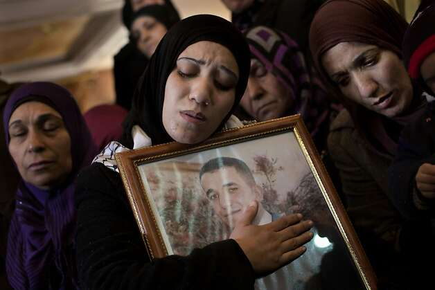 Palestinian women mourn during the funeral of Arafat Jaradat in the West Bank town of Saeer, near Hebron, Monday, Feb. 25, 2013. Thousands have attended the funeral procession of a 30-year-old Palestinian man who died under disputed circumstances in Israeli custody. Palestinian officials say autopsy results show Jaradat was tortured by Israeli interrogators, while Israeli officials say there's no conclusive cause of death yet and that more tests are needed.  Photo: Bernat Armangue, Associated Press