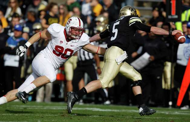 Stanford defensive end Josh Mauro, left, tries to tackle Colorado quarterback Connor Wood duringthe fourth quarter of Stanford's 48-0 victory in an NCAA college football game in Boulder, Colo., on Saturday, Nov. 3, 2012. (AP Photo/David Zalubowski) Photo: David Zalubowski, Associated Press / AP