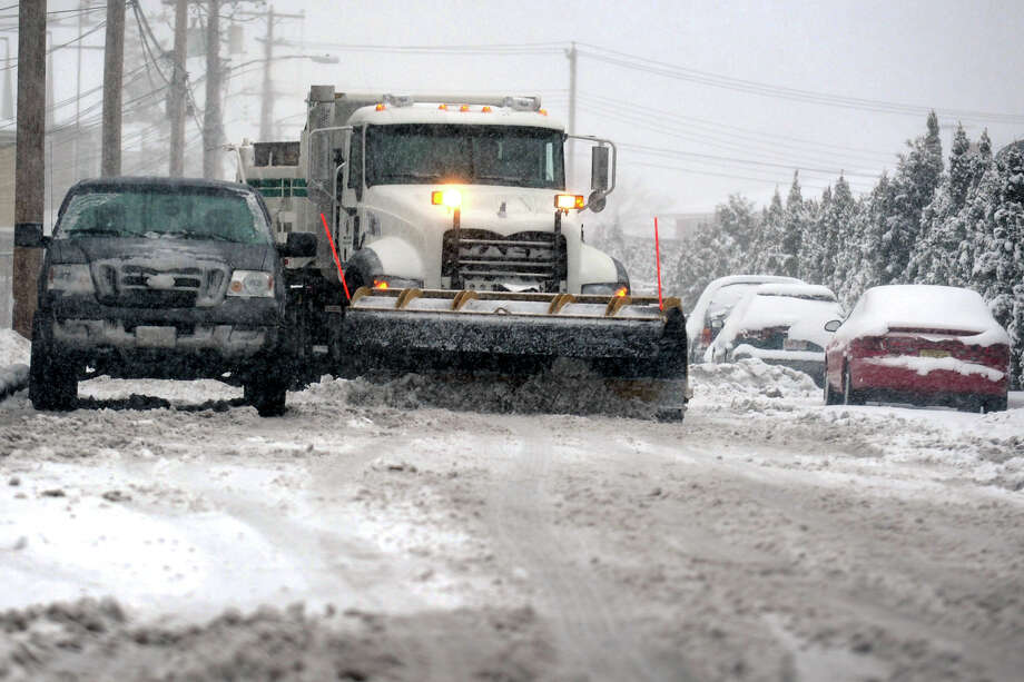 A snow plow works to keep a city street clean in Bridgeport, Conn., Feb. 8, 2013. City officials, who budgeted $100,000 for storm cleanup, said the final cost was $1.7 million. Photo: Ned Gerard / Connecticut Post