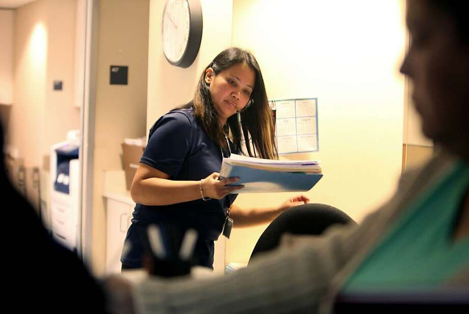 "Administrative intern Lady Mineses works the reception desk at UCSF Occupational Health Services in San Francisco. ""I make more working than staying at home,"" says Mineses, who previously was on CalWORKS and food stamps. Photo: Lea Suzuki, The Chronicle"