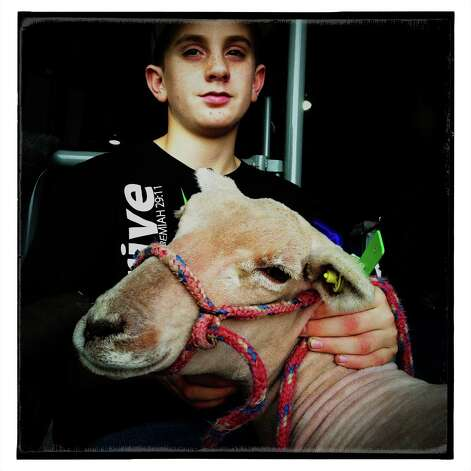 Braden Parsons sits with his lamb in a barn on the grounds of the San Antonio Stock Show and Rodeo on Tuesday, Feb. 12, 2013. This photo was filtered with photography apps on an iPhone. Photo: Billy Calzada, San Antonio Express-News / San Antonio Express-News