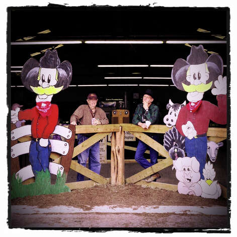 Richard Baer, left, and Greg Young watch from the Animal Adventures barn on the grounds of the San Antonio Stock Show and Rodeo on Tuesday, Feb. 12, 2013. The barn hosts many domestic animals so that children can get a close look at them. Photo: Billy Calzada, San Antonio Express-News / San Antonio Express-News