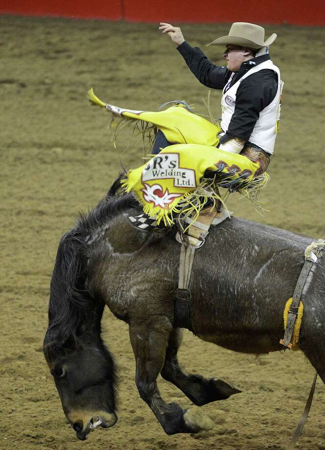 Ty Fast Tapotat struggles to hang on during the bareback riding competition at the San Antonio Stock Show & Rodeo in the AT&T Center on Thursday, Feb. 21, 2013. Tapotat scored a 78 on the ride. Photo: Billy Calzada, San Antonio Express-News / San Antonio Express-News
