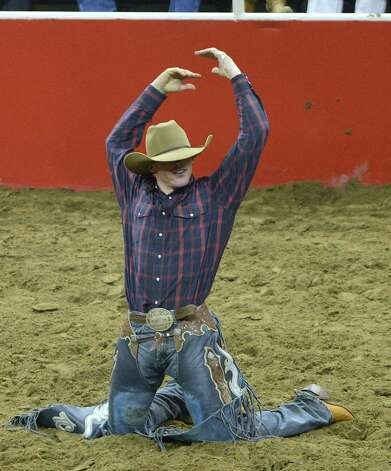 Saddle bronc rider Tyler Corrington asks for applause after his saddle bronc ride at the San Antonio Stock Show & Rodeo on Saturday, Feb. 23, 2013. Corrington scored an 85 on his ride. Photo: Billy Calzada, San Antonio Express-News / San Antonio Express-News