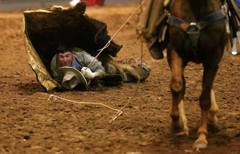 Paloma Cattle Company's Cullen Jurena hangs on during the last leg of the Hide Race competition during the 2013 San Antonio Ranch Rodeo Finals at the San Antonio Stock Show and Rodeo, Sunday, Feb. 24, 2013. Paloma Cattle Company out of Tilden, Texas won second place. Photo: Jerry Lara, San Antonio Express-News / © 2013 San Antonio Express-News