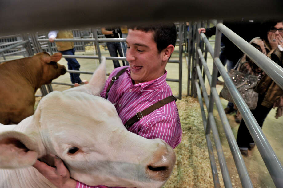 Jonathan Mcanulty hugs his grand champion market steer, Eminem, after it was auctioned at the San Antonio Stock Show and Rodeo for $120,000 Saturday. Photo: Robin Jerstad