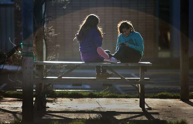 Shellie Ramirez, 13, checks her phone as she sits on a bench with Suzie Perez, 11,  at the Anderson Valley Jr.-Sr. High School in Boonville, Calif. Photo: Lea Suzuki, The Chronicle