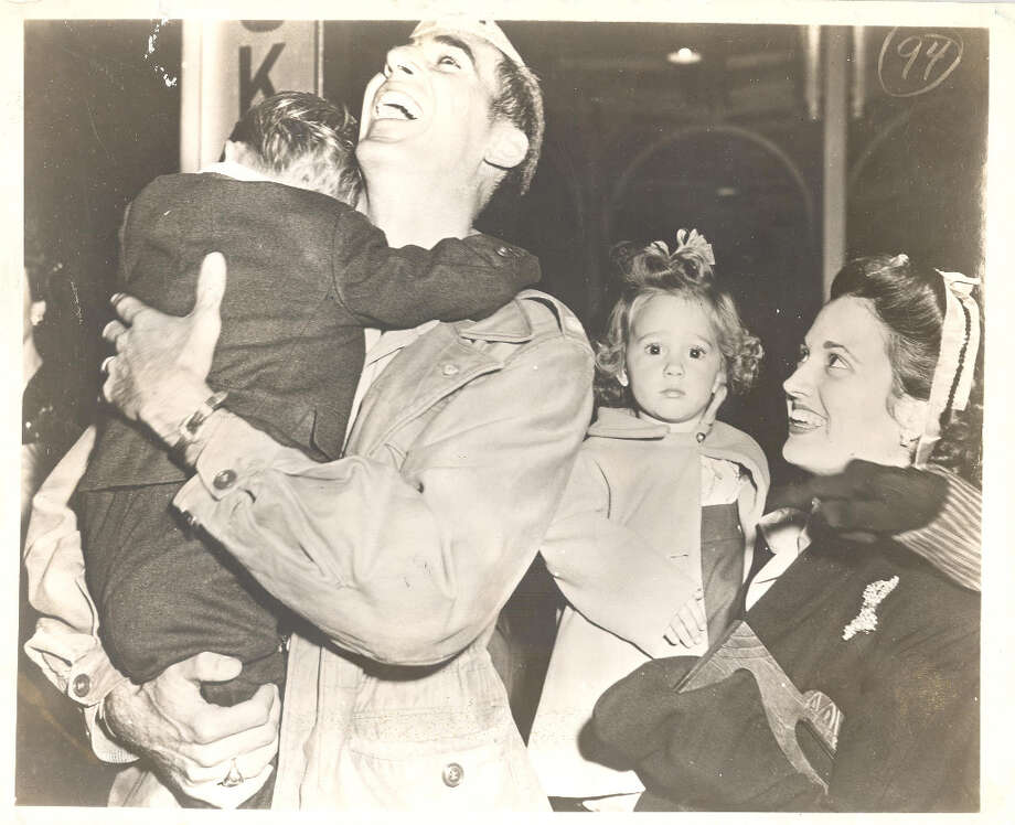 Returning serviceman Lt. Earl Pizzo is greeted by his family at Houston's Southern Pacific Station. Titled 'Daddy, Daddy, Daddy' the picture shows 3-year-old Thomas Earl Pizzo Jr., in his father's arms, and 2-year-old Winnie Jo, bewildered by the fuss, in the arms of her mother. Earlier, the picture won first prize in its class at the Texas Associated Press members photo contest in Dallas. It was made in 1945, given nationwide service by Associated Press wirephoto and has been printed in publications throughout the country. Photo: Caroline Valenta : Post File / email from John Gonzales