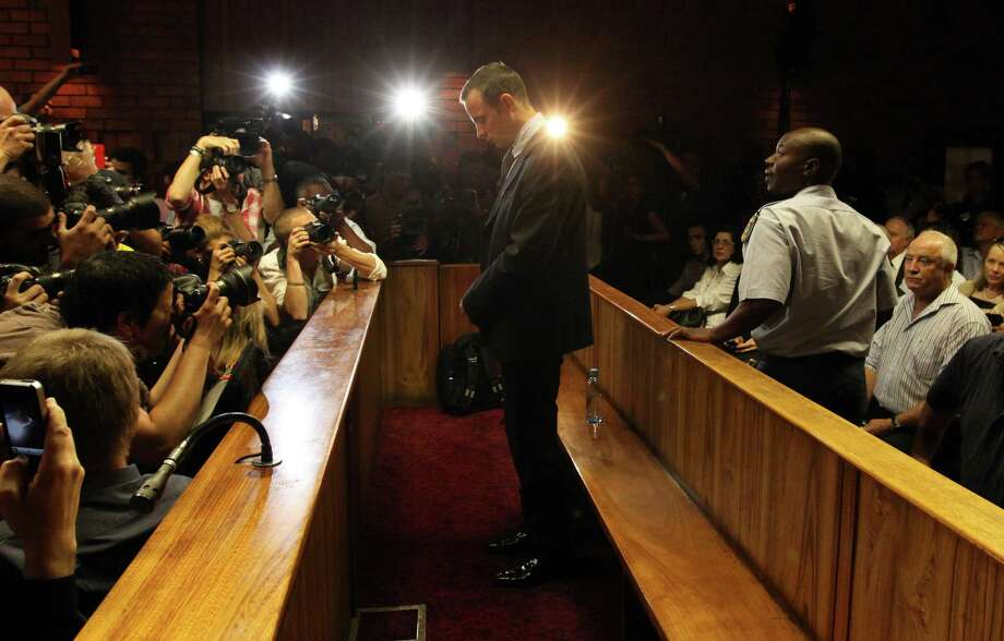 In this photo taken Friday, Feb. 22, 2013, Olympic athlete Oscar Pistorius appears in court during his bail hearing in Pretoria, South Africa, for the shooting death of his girlfriend Reeva Steenkamp. A spokeswoman for Oscar Pistorius says he has reported to authorities under the bail terms in the murder case against him in Preoria, Monday, Feb. 25, 2013. AP Photo/Themba Hadebe) Photo: Themba Hadebe