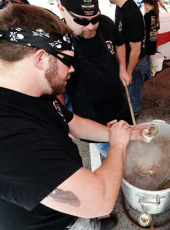 Robert Morris and Jason Farmer serve gumbo in the Beaumont EMS gumbo tent at the 19th Annual Girls' Haven Gumbo Festival at Parkdale Mall on Saturday, February 23, 2013.  Photo taken: Randy Edwards/The Enterprise Photo: Randy Edwards