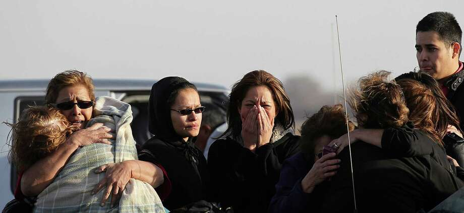 People react at the scene of a multi-structure fire at the 8100 block of Old Pearsall Road, Monday, Feb. 25, 2013. The fire was fueled by high winds and destroyed five houses. Photo: Jerry Lara, San Antonio Express-News / ©2013 San Antonio Express-News