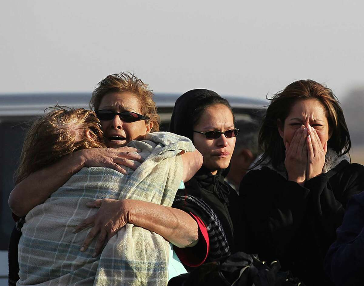 People react at the scene of a multi-structure fire at the 8100 block of Old Pearsall Road, Monday, Feb. 25, 2013. The fire was fueled by high winds and destroyed five houses.