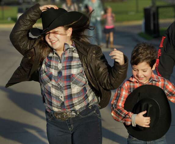 Sasha Amelang, 10 of Houston and her brother Zachary Amelang, 7, holds onto their hats against the wind as they arrive for the rodeo grand entry during the Houston Livestock Show and Rodeo at Reliant Stadium Monday, Feb. 25, 2013, in Houston. Photo: Melissa Phillip, Houston Chronicle / © 2013  Houston Chronicle