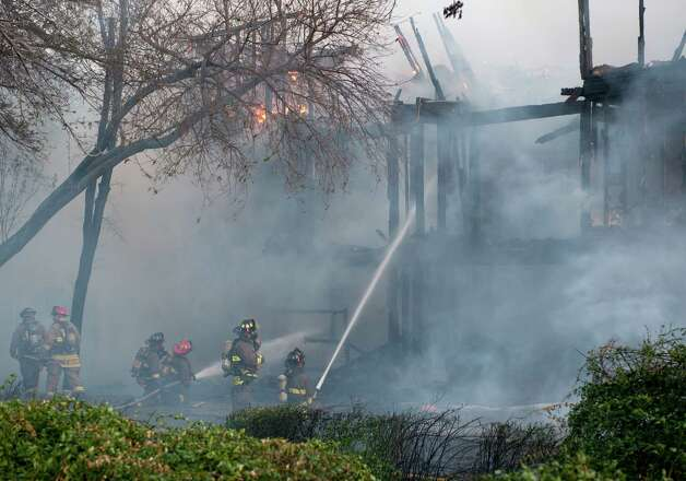 Firefighters spray water onto a structure fire, Monday, Feb. 25, 2013, at an apartment complex in the 10300 block of Sahara St. in San Antonio. Photo: Darren Abate, Darren Abate/For The Express-New