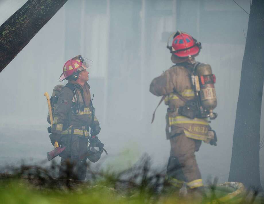 Firefighters survey an apartment unit in flames, Monday, Feb. 25, 2013, in the 10300 block of Sahara St. in San Antonio. Photo: Darren Abate, Darren Abate/For The Express-New