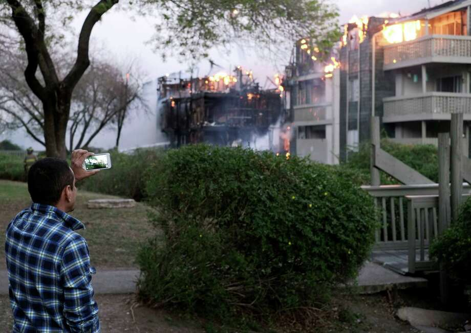 A spectator uses his smart phone to record video of an apartment fire, Monday, Feb. 25, 2013, in the 10300 block of Sahara St. in San Antonio. Photo: Darren Abate, Darren Abate/For The Express-New